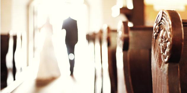 Ein Hochzeitspaar schreitet durch eine Kirche.