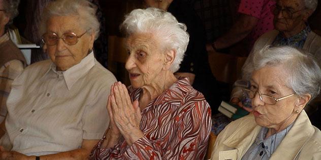 Drei Seniorinnen beim Gebet im Gottesdienst
