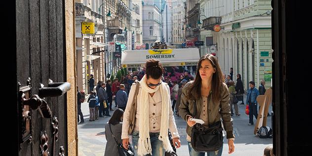 Das Bild zeigt zwei Frauen, die eine Kirche betreten.
