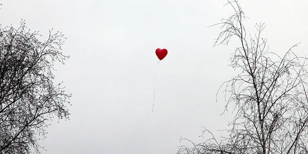 Ein herzförmiger Luftballon steigt gen Himmel